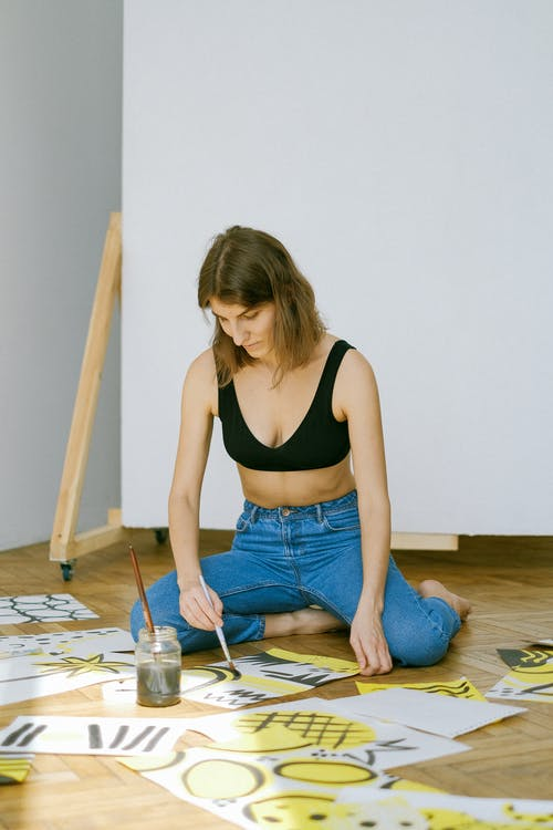 Woman in Black Tank Top and Blue Denim Jeans Sitting on Floor