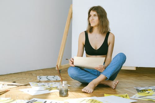 Photo of Woman Sitting on Floor While Looking Serious