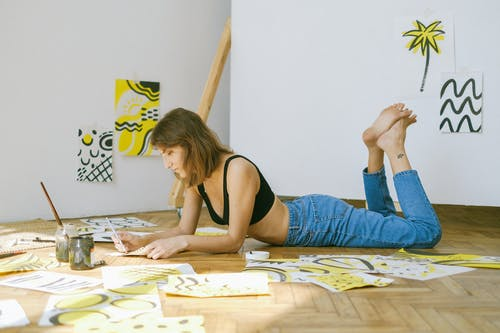 Photo of Woman Lying on Floor While Painting