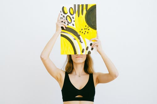 Woman in Black Tank Top Holding Yellow and White Book