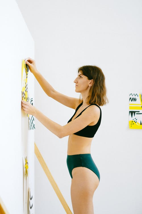 Photo of Woman Posting Her Painting on White Wall