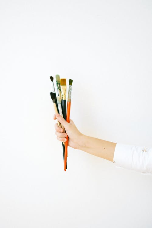 Person Holding Blue and Brown Paint Brush