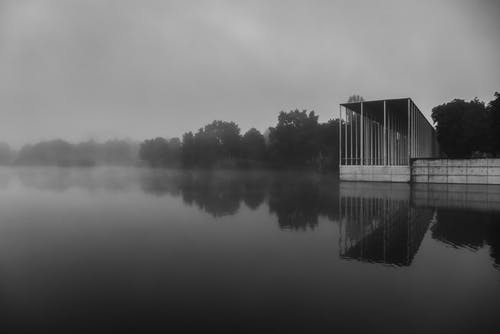 Grayscale Photo of Wooden House on Lake