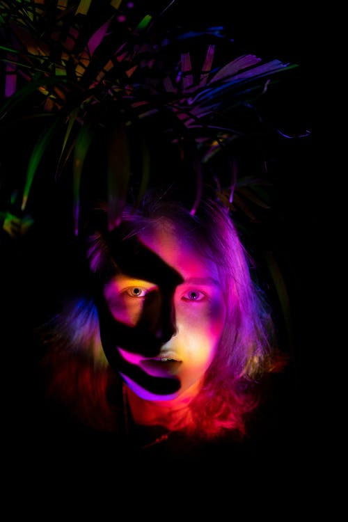 Young female illuminated by colorful neon lights with shadow on face standing in darkness against bush