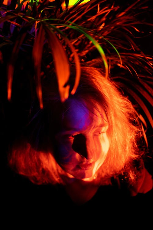 High angle of young female with wavy hair and illuminated face sitting under tropical plant in darkness with neon lights