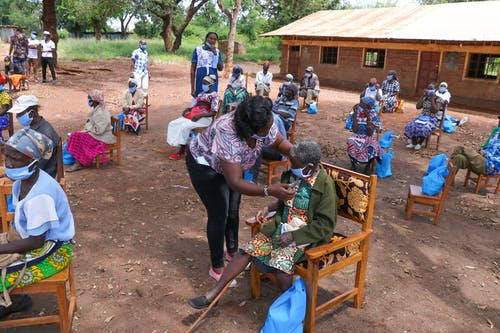 Black elderly people sitting on chairs in yard of hospital in poor African village