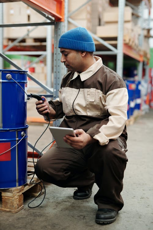 Man in Brown Jacket and Blue Knit Cap Sitting on Blue Plastic Trash Bin