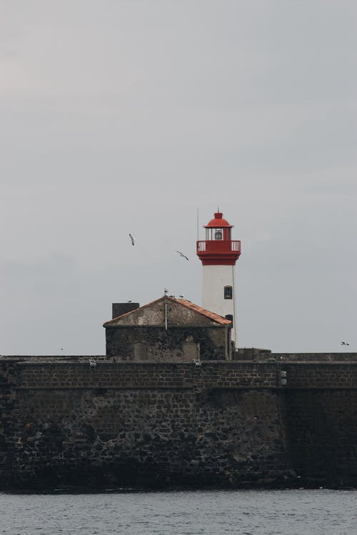 Red and white lighthouse tower located on stony embankment of sea against gray cloudy sky with flying birds