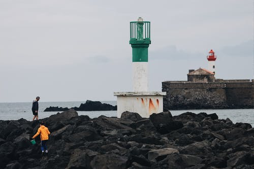Unrecognizable people walking on rough stony breakwater with lighthouse tower in gray overcast weather  on seashore