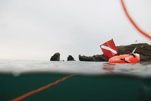 Red inflatable buoy with scuba flag floating in sea water near rocky formations