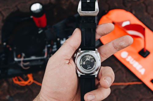 Person Holding Black and Silver Round Analog Watch