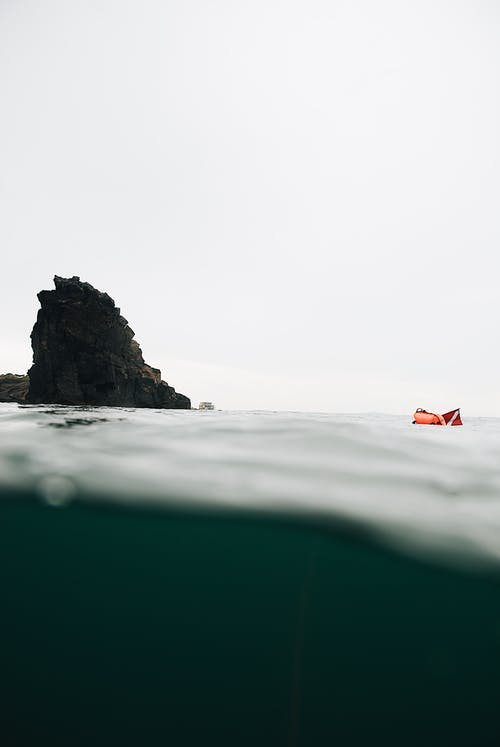 Steep rock and inflatable boat over sea surface