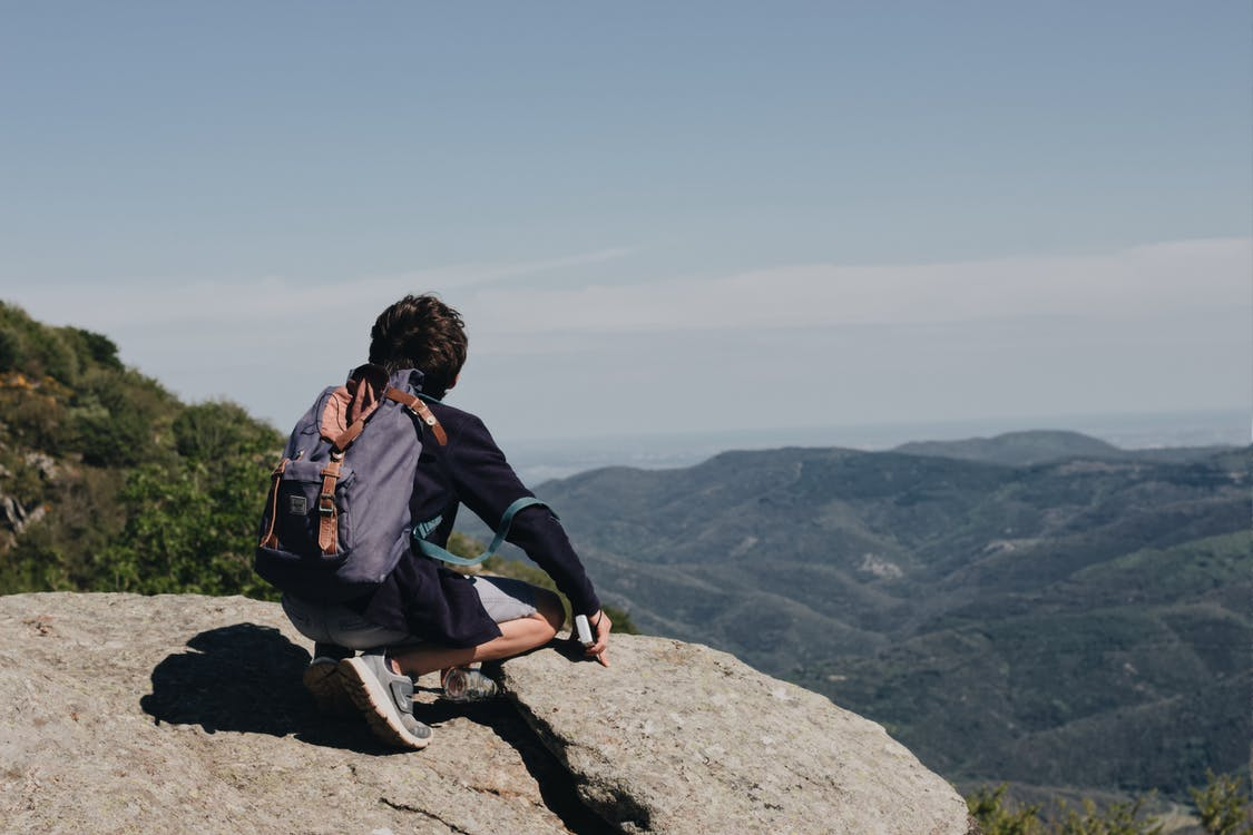 Photo of Person Wearing Backpack While Sitting on Rock