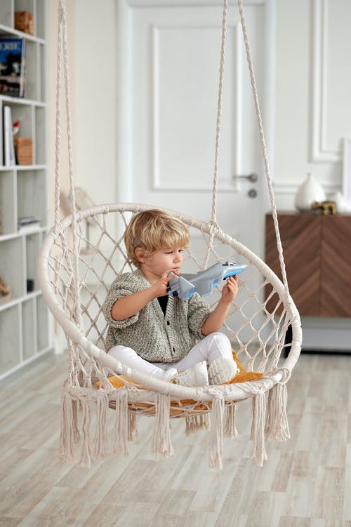 Photo of Child Sitting on Wicker Swing While Playing With Toy Plane