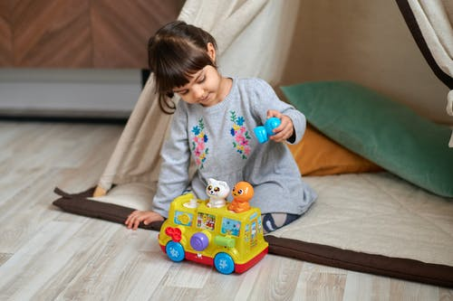 Photo of Girl Playing With Plastic Toy Car