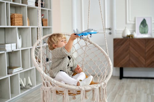 Boy Sitting on Wicker Swing While Playing With Toy Plane