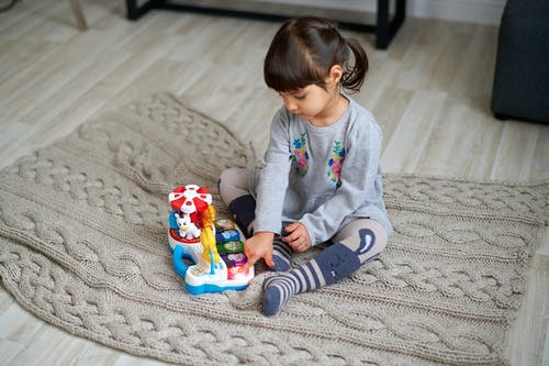 Girl in Gray Sweater Playing With Plastic Toy