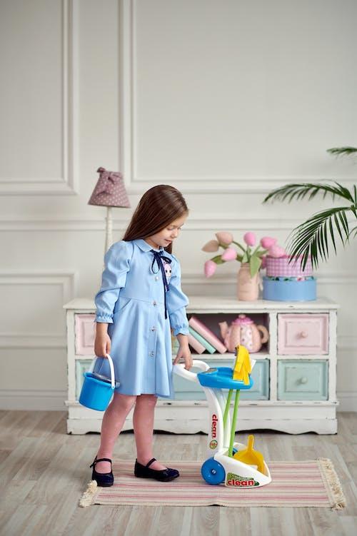 Girl in Blue Dress Holding a Blue Bucket