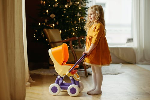 Girl in Orange Dress Standing While Holding Baby Stroller