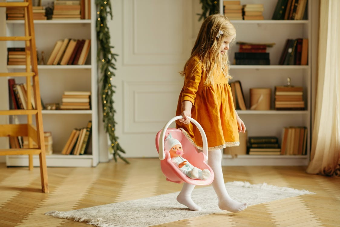 Girl in Orange Dress Walking While Carrying Baby Doll