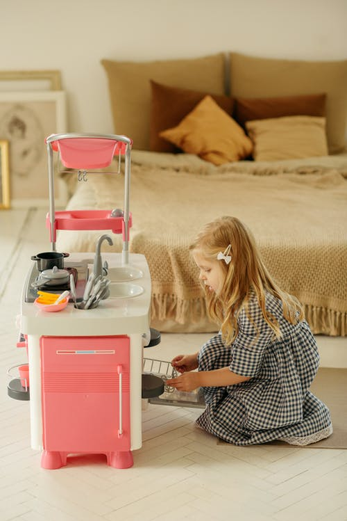 Girl in Black and White Checkered Dress Shirt Playing With Kitchen Plastic Toy