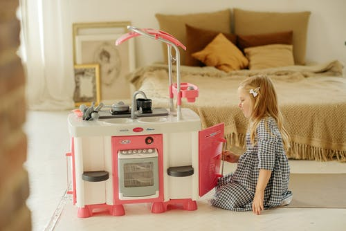 Photo of Girl in Plaid Dress Playing With Kitchen Toy