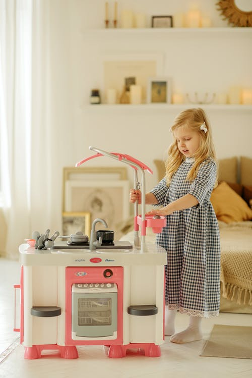 Girl in Plaid Dress Playing With Kitchen Toy