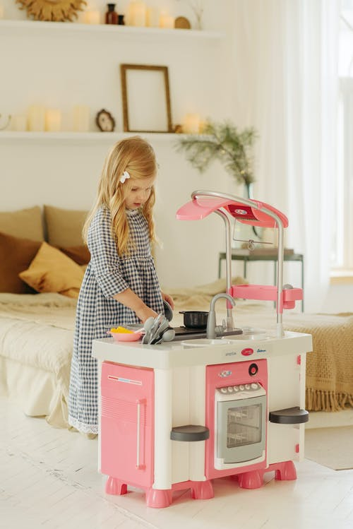 Woman in Black and White Checkered Dress While Playing With Kitchen Plastic Toy