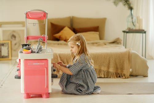 Girl in Black and White Checkered Dress Playing With Kitchen Plastic Toy