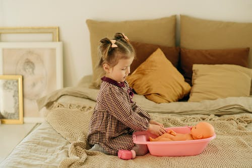 Girl in Plaid Dress Sitting on Bed While Playing With Baby Doll