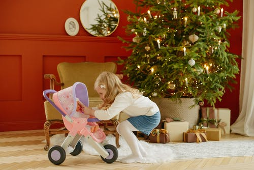 Girl in White Long Sleeve Shirt Playing With Baby Doll in Baby Stroller