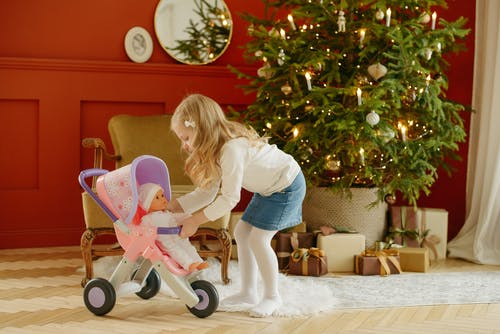 Photo of Girl Playing With Baby Doll in Baby Stroller
