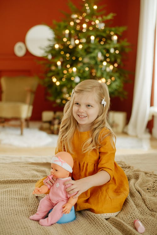 Girl in Orange Dress Smiling While Holding Baby Doll