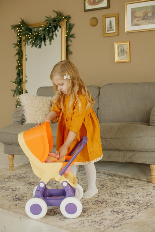 Girl in Orange Dress Playing With Baby Doll in Baby Stroller