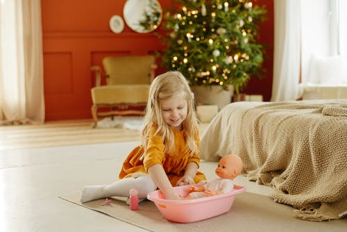 Girl in Orange Dress Playing With Baby Doll