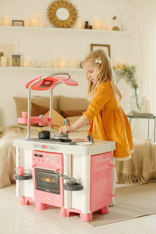 Photo of Girl Playing With Kitchen Plastic Toy