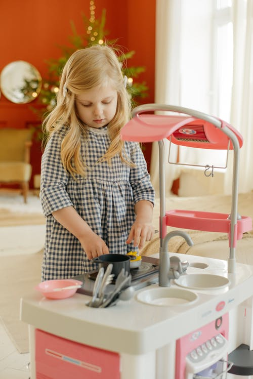 Girl in White and Black Checkered Dress Shirt Playing With Kitchen Plastic Toy