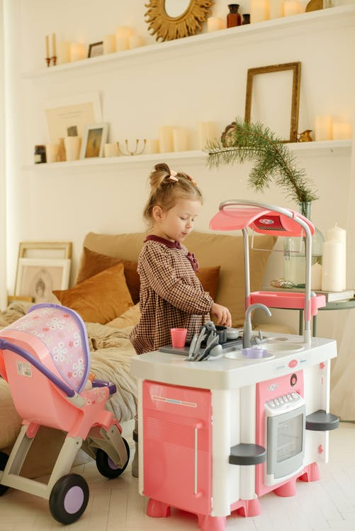 Girl in Plaid Dress Playing With Kitchen Plastic Toy