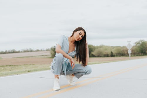 Woman in White Long Sleeve Shirt and Blue Denim Jeans Sitting on Gray Concrete Road during