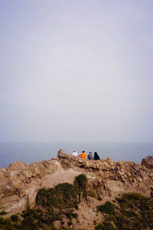 Travelers admiring sea from rocky coast