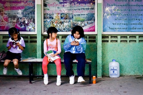 Asian schoolgirl browsing smartphone while sitting with classmates on bench near school building after lesson