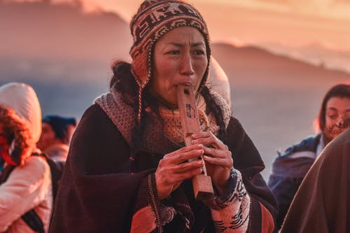 Man in Brown and White Scarf Holding Flute