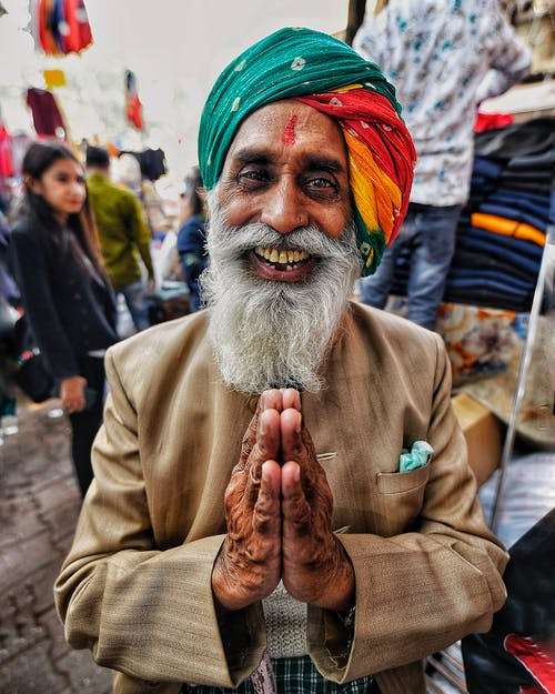 From above of cheerful senior Indian male in bright head wear with gray beard standing with prayer hands and looking at camera in town