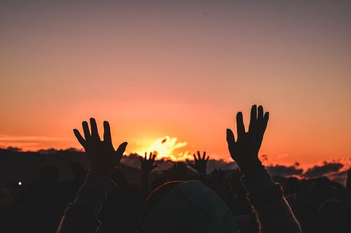 Silhouette of People Raising Their Hands during Sunset