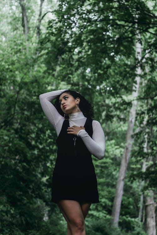 Stylish ethnic woman touching hair near trees
