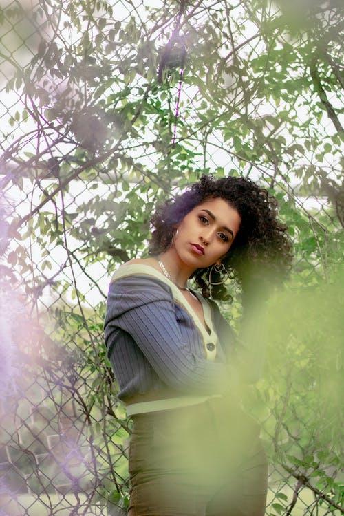 Stylish ethnic woman with tilted head among trees