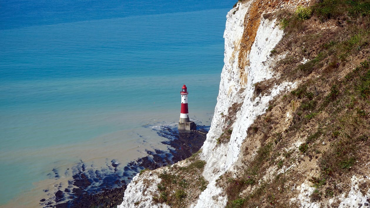 Red and White Lighthouse Near Body of Water