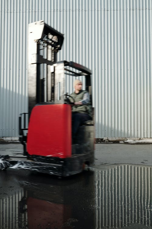 Man in Gray Jacket Sitting on Red and Black Metal Machine