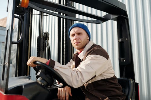 Close Up Photo of Man Seated on a Heavy Equipment