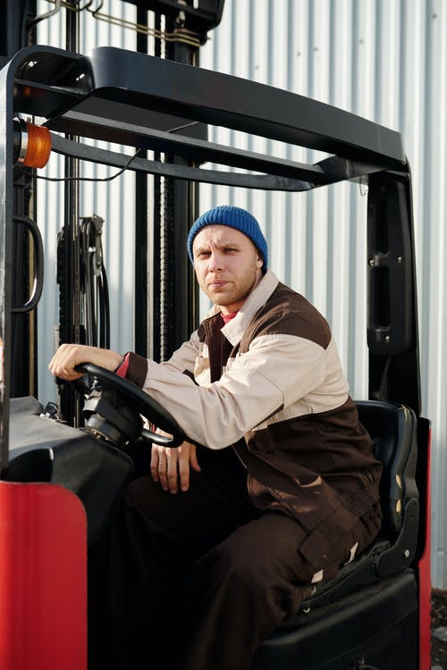 Man in White Dress Shirt and Blue Knit Cap Sitting on Black and Red Auto Rickshaw